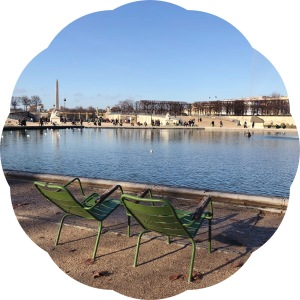 Chairs around a pond in the Tuileries gardens on a sunny day